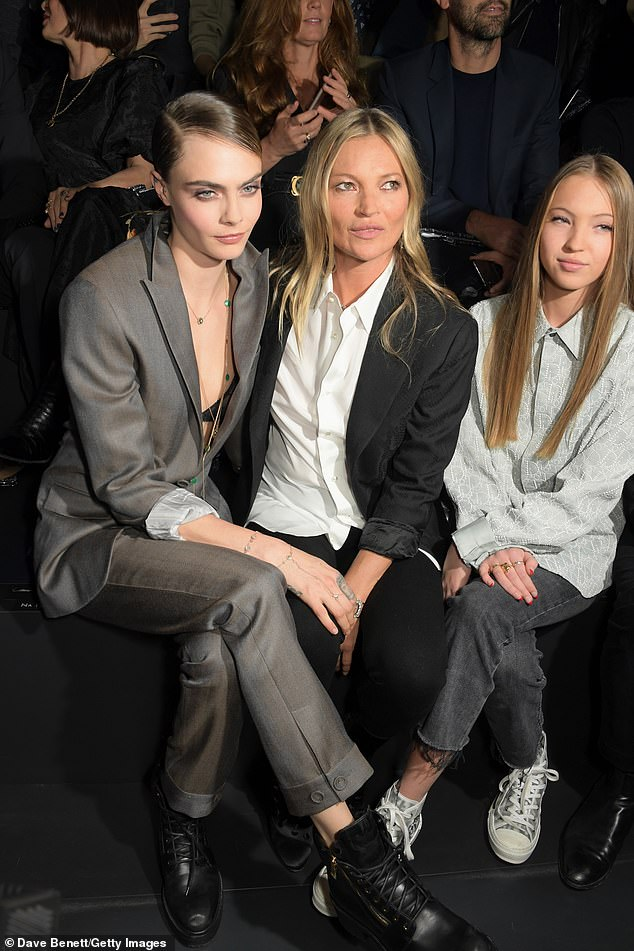 What a trio: The pair were in good company at the show, as they sat alongside model Cara Delevingne, 27