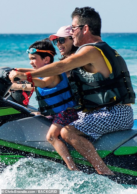 Time of his life: Eric was thoroughly enjoying his jet ski ride with his famous parents