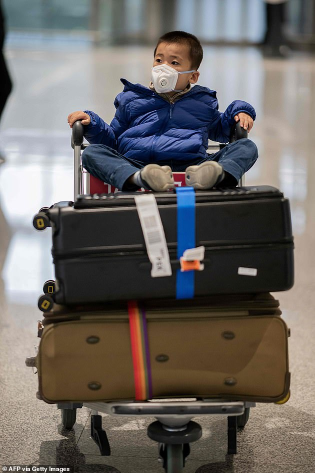 A child wears a facemask at Daxing international airport in Beijing as he heads home for the Lunar New Year