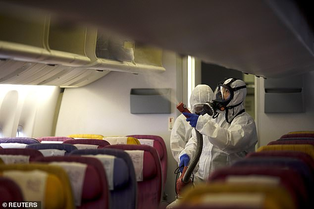 Thai Airways employees are pictured disinfecting an empty plane cabin atSuvarnabhumi International Airport in Bangkok today, January 28. Thailand has 14 confirmed coronavirus cases – the most outside of China
