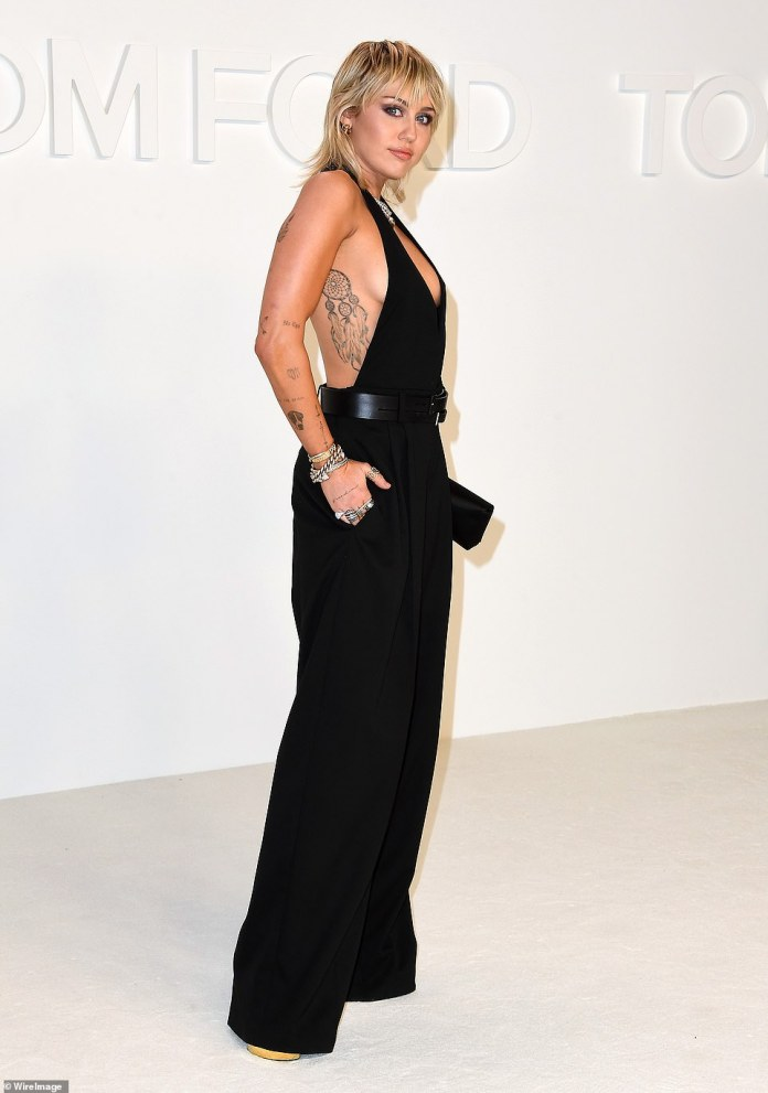 She's got some front! Wrecking Ball songstress Miley showed plenty of front in a black jumpsuit with a deep plunging neckline