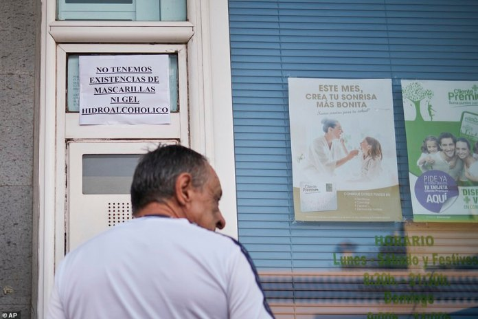 A Spanish note hanging on the window of a pharmacy in Tenerife reads: 'We do not have masks or hydroalcoholic gel stocks'