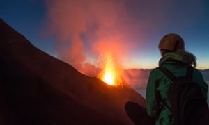 Young woman watching volcanos' eruption at Stromboli