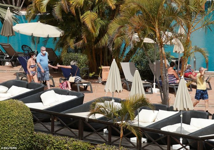 Tourists with masks are seen near the pool of H10 Costa Adeje Palace, which is on lockdown after cases of coronavirus have been detected