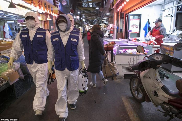 Disinfection workers in protective gear sterilize the Tong-in Market in Seoul amid fears of the killer coronavirus spreading throughout South Korea