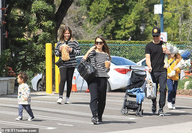 Multitasking:Cash's arms were full of groceries for the family and with one free hand he pushed along a stroller that had what looked like a denim jacket thrown onto it