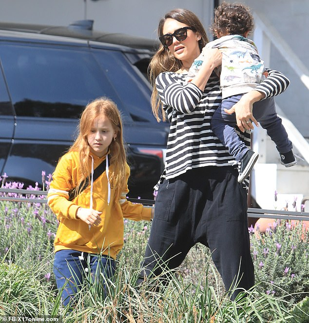 Baby mine:As he kept his eye on their shopping Jessica could at one point be spotted scooping up her youngest child into her arms