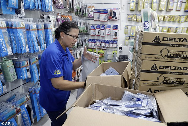 No on-site safety and quality checks have been conducted since December and they are suspended at least March. Pictured: A worker at a medical supply store organizes masks
