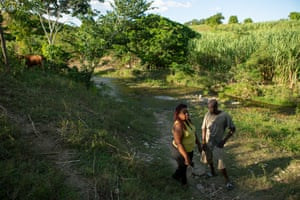 Marie Millande Tulmé, an epidemiologist, speaks with Reynald Louis Charles, a farmer, on the banks of the Meille river at the former UN base near Mirebalais