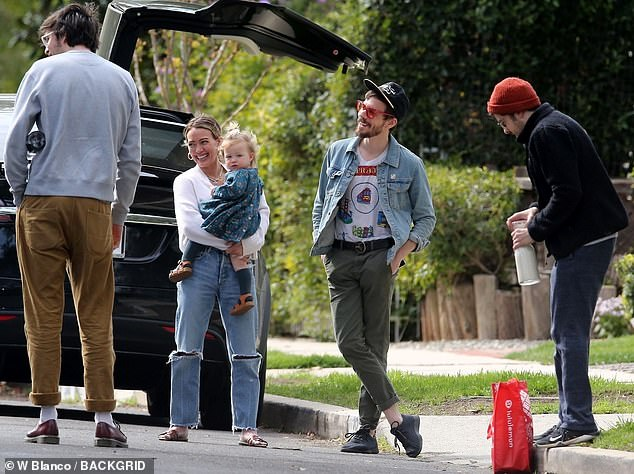 Old friends: The family appeared to receive a drop-off of supplies from a couple of pals including actor Christopher Mintz-Plasse (right), their wedding officiant