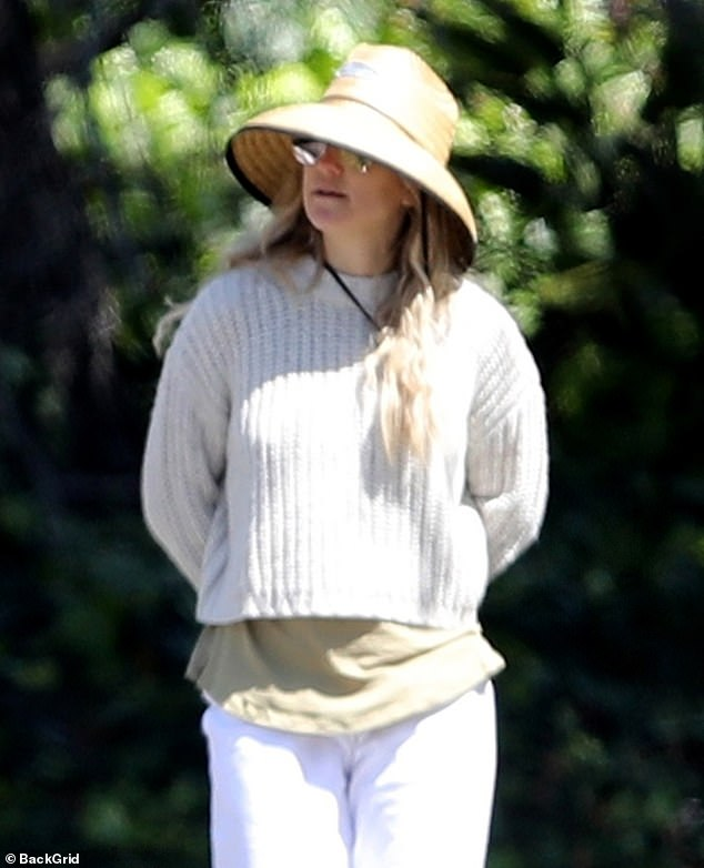 White on! The mother-of-three went for an all-white ensemble for the afternoon amble, pairing an off-white sweater with loose, white linen pants