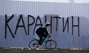 "A woman rides a bicycle in front of the fence with the graffiti reading ""quarantine' in Minsk, Belarus, Monday, April 6, 2020."