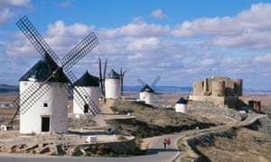 Windmills and castle overlooking the plains of Castilla La Mancha, Spain; image shows a couple walking together.