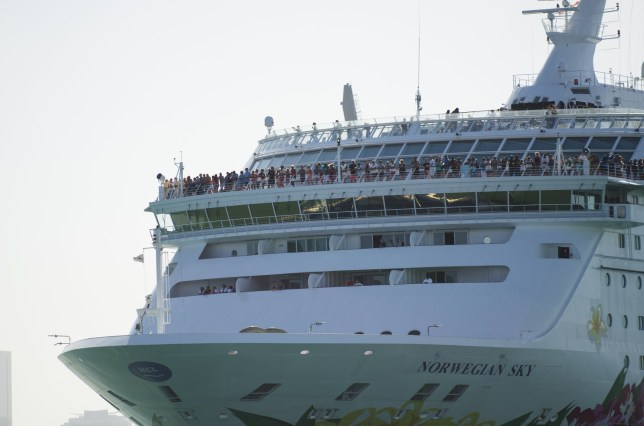 Passengers on the Norwegian Sky cruise ship look out over South Beach as it leaves PortMiami