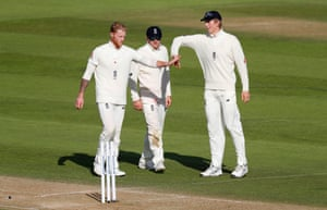Ben Stokes of England celebrates with Dom Bess and Zak Crawley after taking the wicket of Alzarri Joseph.