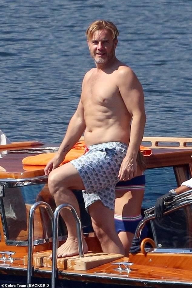 Time for a swim:Gary Barlow, 49, stripped down to blue swimming trunks as he and wife Dawn Andrews, 50, enjoyed a swim during their Lake Como trip on Friday