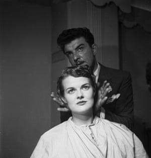 Raymond, 'Mr Teasy Weasy' admires a hairstyle he has created, 1952.