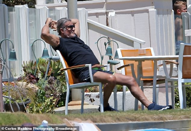 And relax:The star paired his trendy ensemble with black trainers and a stylish pair of shades, with his silver locks worn in a tousled style