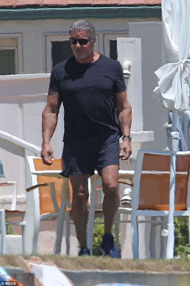 Off we go: The star displayed his hunky frame as he walked down the beach