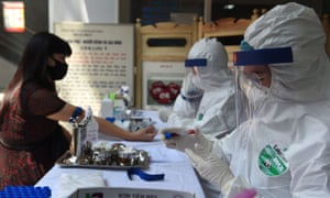 A health worker wearing protective clothing amid concerns of the spread of Covid-19 takes a blood sample from a resident at a makeshift rapid testing centre in Hanoi.
