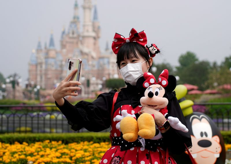 © Reuters. FILE PHOTO: A visitor dressed as a Disney character takes a selfie while wearing a protective face mask at Shanghai Disney Resort as the Shanghai Disneyland theme park reopens following a shutdown due to the coronavirus disease (COVID-19) outbreak, in Sha