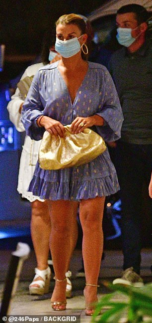 Lovely: The WAG showed off her tanned pins in a blue spotted wrap dress with metallic accessories