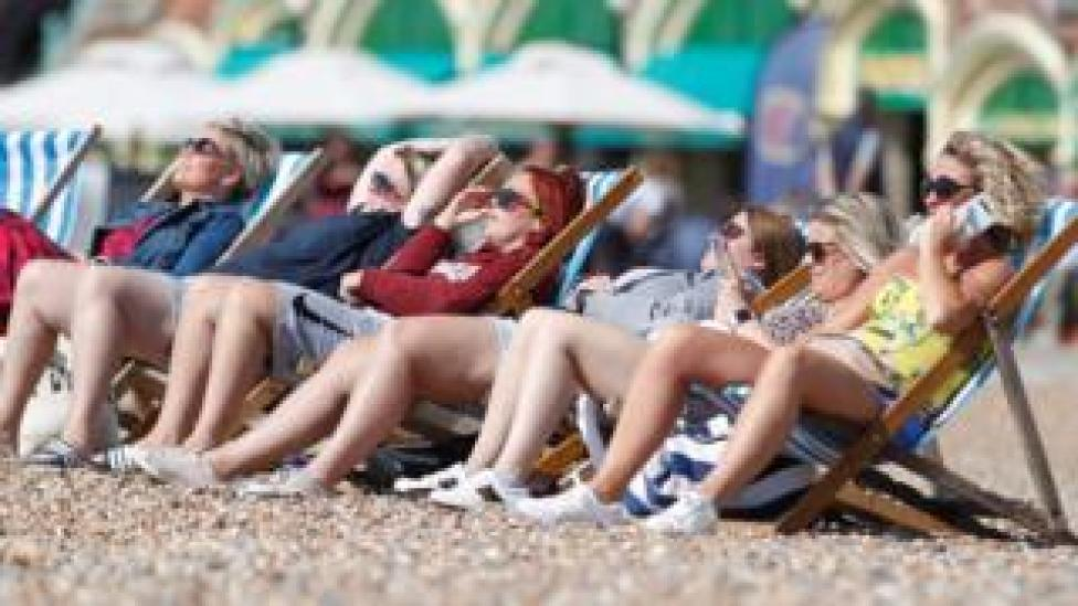 A group of women sit in the sunshine on the beach in Brighton, Britain