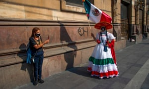 A woman in a traditional Mexican attire and wearing a protective face mask poses for a photo the day before the commemoration of the 210th anniversary of the Mexican Independence in Mexico City, on 15 September 2020, amid the coronavirus pandemic.