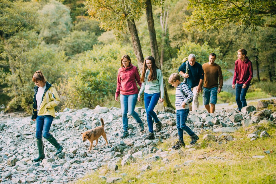 Three generation family are hiking together through the Lake District with their pet dog.