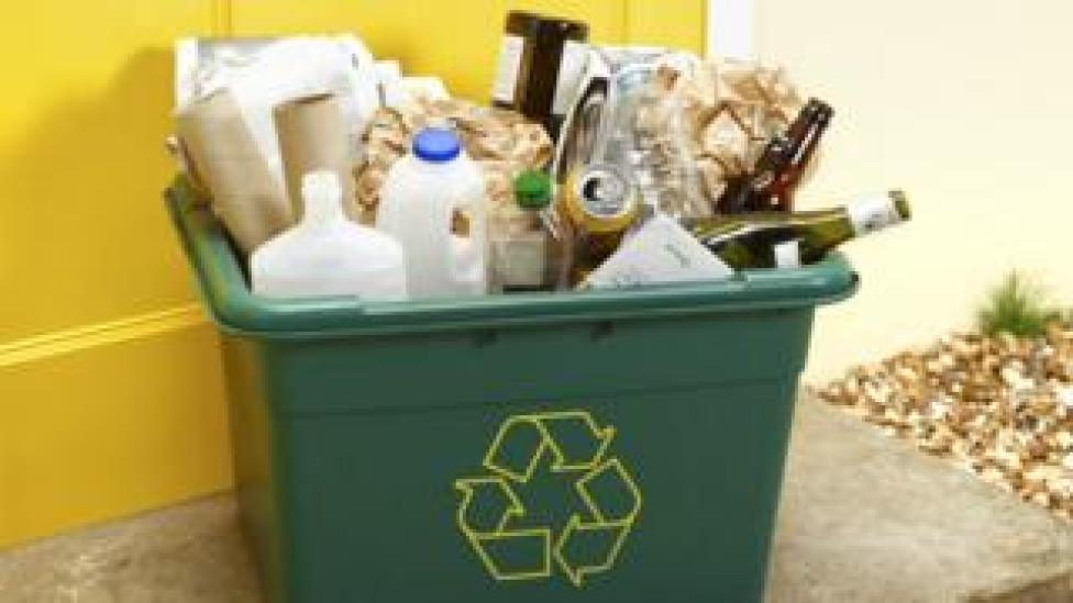 Full household recycling bin - glass bottles, milk bottles and paper wrapping visible