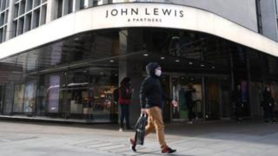 Shopper walking past John Lewis storefront