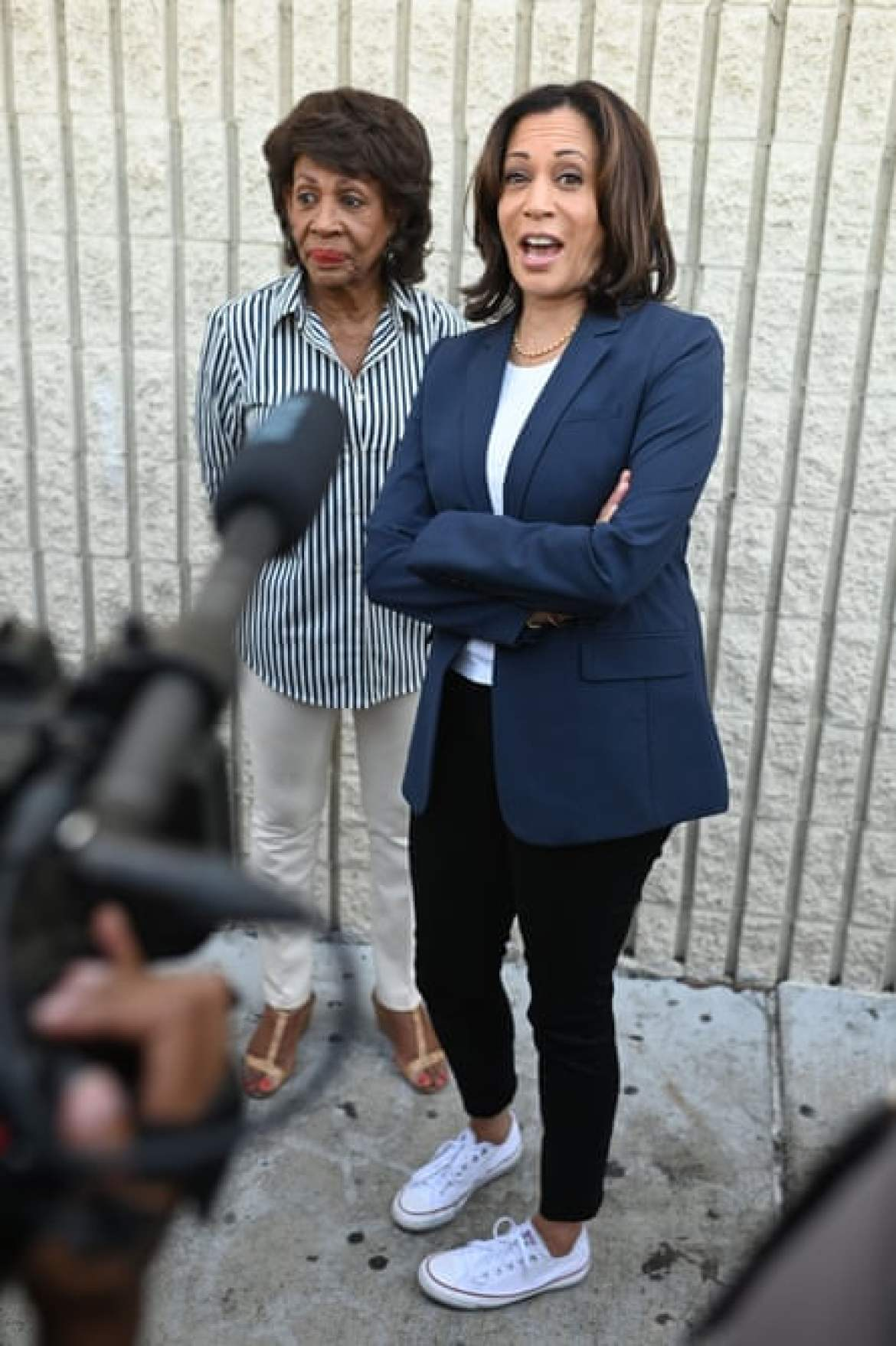 Kamala Harris speaks to the media accompanied by Congresswoman Maxine Waters at a Labor Day rally for healthcare workers last September.