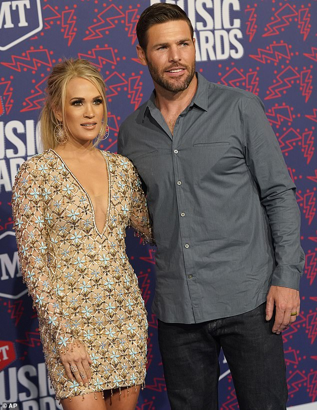 Decade of love: Carrie and Mike first met after they were set up by a mutual friend. Fisher ended up coming backstage at one of her concerts and the rest was history; pictured at the CMT Awards June 2019
