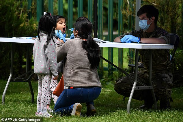 Britons who show Covid symptoms can apply for drive-through tests, but some have revealed they are directed to centres more than 100 miles away (Pictured:A family member administers a self-test to a child at a station in Leicester)