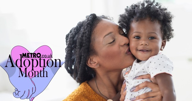 Smiling mother kissing baby daughter on cheek