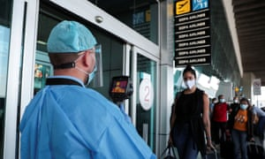 A healthcare worker measures the temperatures of travelers before entering the Tocumen International Airport during the coronavirus outbreak, in Panama City, Panama 16 October 2020.