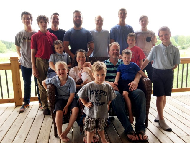 FILE - In this May 30, 2018 file photo, the Schwandt family poses for a photo at their farm in Lakeview, Mich. Standing from left are Tommy, Calvin, Drew, Tyler, Zach, Brandon, Gabe, Vinny and Wesley. Seated, starting at upper left are Charlie, Luke, mother Kateri holding Finley, father Jay with Tucker and Francisco in the foreground. The 14-boy family has welcomed their first daughter nearly three decades after the birth of their first child. Kateri Schwandt gave birth to Maggie Jayne Schwandt Thursday, Nov. 5, 2020, at a hospital in Grand Rapids, Mich. (AP Photo/Mike Householder, File)