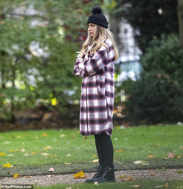 Low-key: She cut a casual figure in the cosy red printed coat with chunky boots as she headed to the park to meet her ex