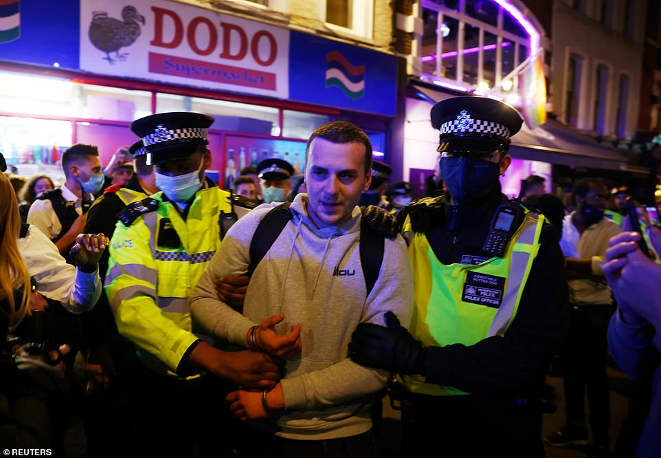 The man was arrested, although it is unclear what he was arrested for. He is pictured being led away by police officers in Soho