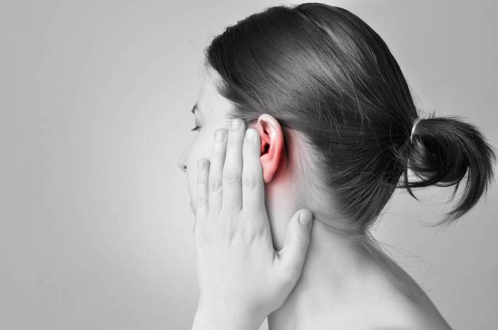 A young woman touching her painful ear