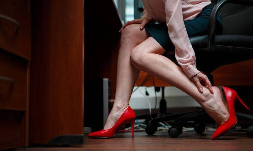 bigstock-Business-woman-touching-feet-w-132139841