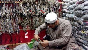 A worker busy in fixing beads in necklaces | Photo by News Lens Pakistan.