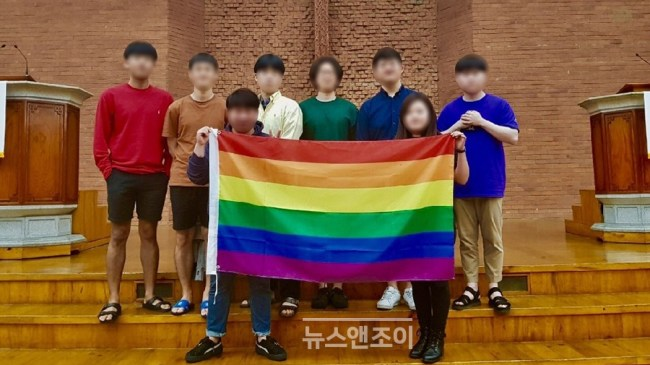 Students hold up a rainbow flag to stand against homophobia. They are dressed in rainbow colors and standing on the steps of a church chapel.