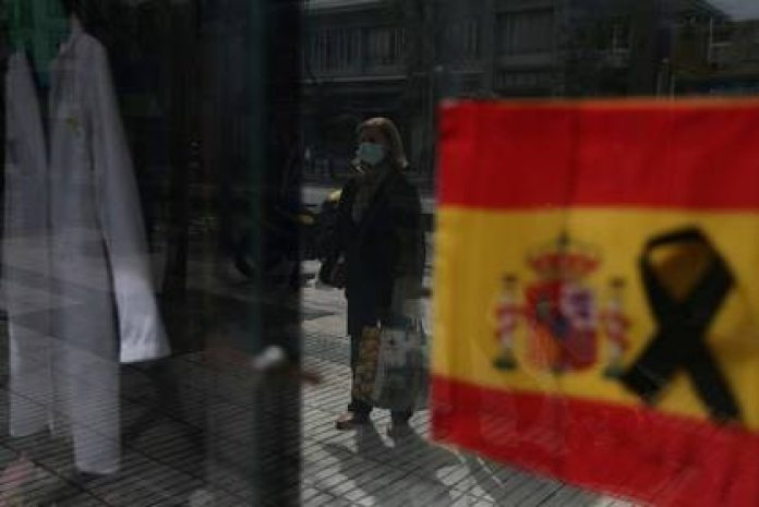 A woman with a protective mask waits to enter a pharmacy showing a Spanish flag with a black tie, in the midst of the outbreak of coronavirus disease (COVID-19) in Madrid, Spain, on April 18, 2020. REUTERS / Susana Vera / Photo Archive
