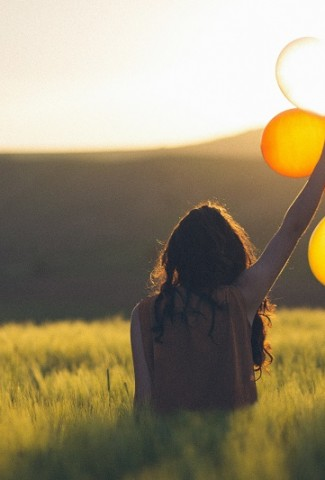 Herbalife Immune Health Benefits Woman Sitting in a Field Holding Balloons