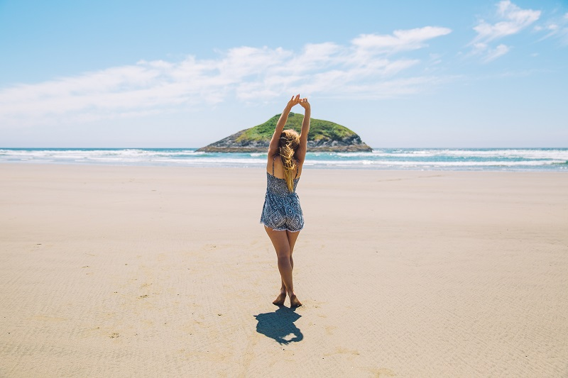 Herbal Aloe Bath & Body Care Products Woman Standing on a Beach Stretching Her Arms Upward