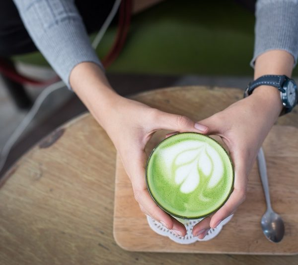 Energy Boosting Tea Recipes Overhead View of a Person Holding a Cup of Green Matcha Tea