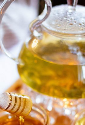 Immune Boosting Tea Recipes a Person Using a Honey Dipper with a Glass Tea Pot Filled with Tea in the Background
