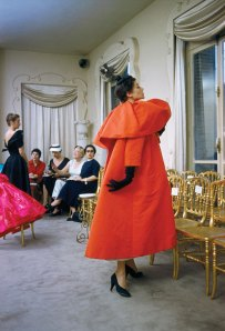 Mark Shaw. Model wearing Balenciaga orange coat as I. Magnin buyers inspect a dinner outfit in the background, Paris, France, 1954. © Mark Shaw, mptvimages.com.