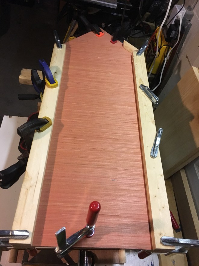 Plywood sides clamped with pine strapping.